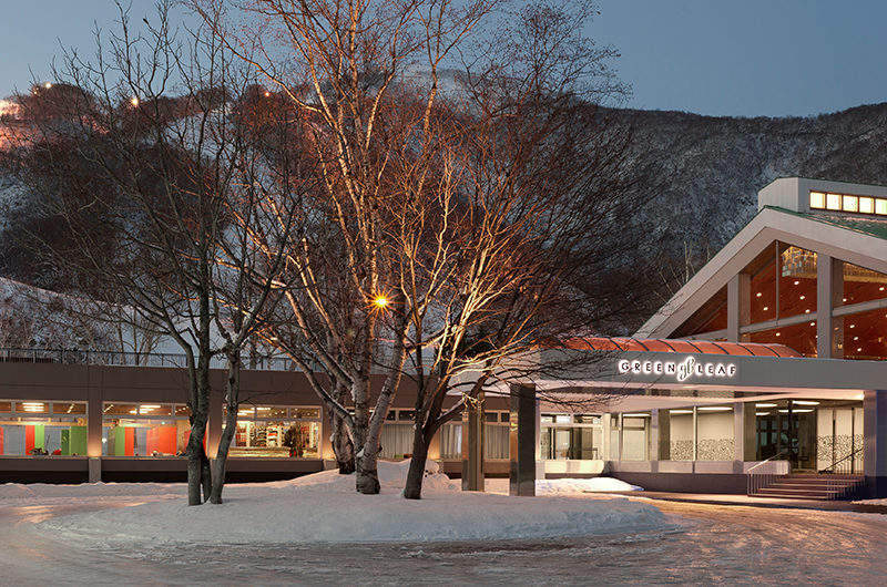 Green Leaf Niseko Village Hotel Entrance with Ski Runs in the Background | Niseko Village
